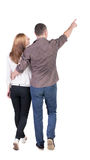 Back view of walking young couple (man and woman) pointing. Stock Photos