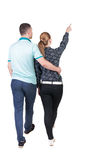 Back view of walking young couple (man and woman) pointing. Rear view people collection. backside view of person. Isolated over white background. Wife shows Stock Images