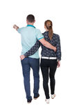 Back view of walking young couple (man and woman) pointing. Royalty Free Stock Image