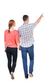 Back view of walking young couple (man and woman) pointing. Stock Image
