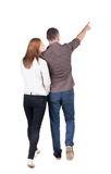 Back view of walking young couple (man and woman) pointing. Royalty Free Stock Photo