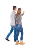 Back view of walking young couple. (man and woman) pointing. Rear view people collection. backside view of person. Isolated over white background/ pressed Royalty Free Stock Images