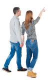 Back view of walking young couple. (man and woman) pointing. Rear view people collection. backside view of person. Isolated over white background The girl Stock Photos