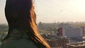 Back view. Wind blows long dark hair beautiful young women. girl standing on the roof at sunset. Slow mo. Back view. Wind blows long dark hair beautiful young stock video footage