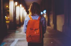 Back view woman with backpack on background bokeh light in night atmospheric city, blogger hipster planing holiday travel, mockup. Street, online wifi internet royalty free stock photos