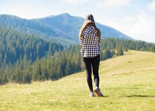 Back view woman with backpack on top of mountains looking to nature valley. Back view young woman with backpack on top of mountains looking to nature valley royalty free stock images