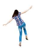 Back view woman Balances waving his arms.   Standing young girl. In jeans. Rear view people collection.  backside view of person.  Isolated over white Royalty Free Stock Photography