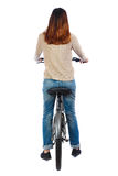 back view of a woman with a bicycle. cyclist sits on the bike Stock Photos