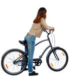 Back view of a woman with a bicycle. cyclist sits on the bike Royalty Free Stock Image