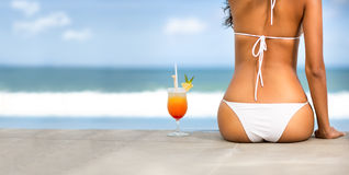 Back view of woman in bikini on beach. Back view of young woman in bikini with cocktail on beach Royalty Free Stock Photography