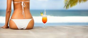 Back view of woman in bikini on beach. Back view of young woman in bikini with cocktail on beach Stock Image