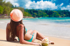 Back view of woman in bikini with coconut drink relaxing at tropical beach Stock Photo