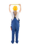 Back view of woman in blue builder uniform holding measure tape Royalty Free Stock Image