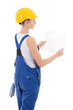 Back view of woman builder in blue coveralls holding building sc Stock Photo