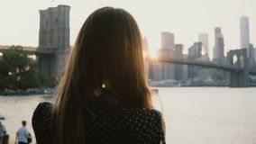 Back view woman with camera taking photos of amazing Brooklyn Bridge sunset cityscape panorama in New York City 4K. stock video