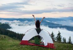 Attractive naked woman in camping. Back view of woman camper standing in the tent entrance in sleeping bag, lifting hands up in the air, enjoying beautiful view stock photos