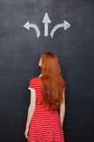 Back view of woman choosing direction over chalkboard background Royalty Free Stock Photos