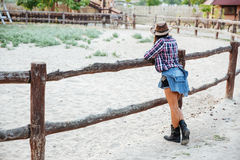 Back view of woman cowgirl standing near fence on ranch. Back view of young woman cowgirl in hat standing near fence on ranch stock photos
