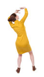 Back view woman in a dress protects hands from what is falling f Royalty Free Stock Image