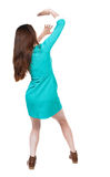 Back view woman in a dress protects hands from what is falling f Stock Photos