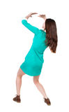 Back view woman in a dress protects hands from what is falling f Stock Photo