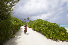 Back view of woman and girl riding bike on a path by a beach Royalty Free Stock Photo