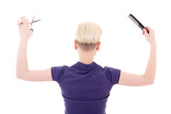 Back view of woman hair stylist posing with comb and scissors is Royalty Free Stock Photography