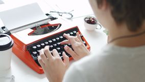 Woman hand typing on red vintage typewriter. Back view of woman hand typing on red vintage typewriter stock video footage