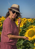 Back view of woman in hat looking at sunflower Stock Image