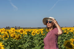 Back view of woman in hat looking at sunflower Stock Photography