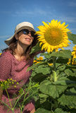 Back view of woman in hat looking at sunflower Royalty Free Stock Images