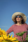 Back view of woman in hat looking at sunflower Stock Photos