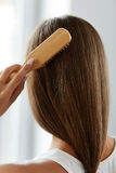 Back View Of Woman With Healthy Long Hair Brushing It With Brush. Beautiful Healthy Hair. Closeup Of Woman Hand Brushing Natural Long Brown Hair With Wooden stock photos