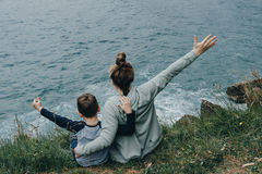 Back view of woman and her son raised their hands upwards sittin. Back view of women and her son raised their hands upwards sitting on the mountain above the sea Royalty Free Stock Image