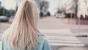 Back view woman with long blonde hair walking. Businesswoman in blue coat with beautiful long fair hair. Slow motion. Back view woman with long blonde hair stock footage