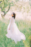 The back view of the woman in the long white dress and with the accessories on her hair in the green spring field. Royalty Free Stock Photography