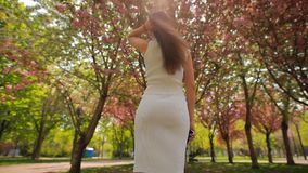 Back view of woman looking at blossom trees in summer park touching hair. Back view of woman looking up at blossom trees in summer park touching her brown hair stock video