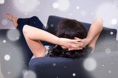 Back view of woman lying on sofa at home Stock Images