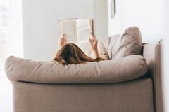 Back view of woman lying and reading book. Back view of woman lying on sofa and reading book at home Royalty Free Stock Photo