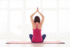 Back view of woman meditating with hands raised above the head Royalty Free Stock Photos