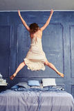 Back view of a woman in nightgown jumping on bed with arms and l Stock Images