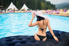 Back view woman with perfect figure in a black bikini and hat sit on a mattress in the swimming pool on resort. Against blurred background of forest and hills royalty free stock photos