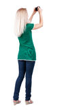 Back view of woman photographing. girl photographer in jeans. Re Stock Images