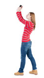 Back view of woman photographing.   girl photographer in jeans. Royalty Free Stock Photo