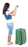 Back view of woman photographing traveling with suitcas. Stock Photo