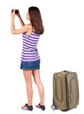 Back view of woman photographing traveling with suitcas. Royalty Free Stock Image