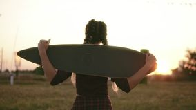 Back view of woman in plaid shirt and tank top holding longboard and walking during the sunset in summertime. Lens flare. Slowmotion shot stock footage