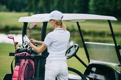 back view of woman in polo and cap with golf gear standing at golf cart at golf course