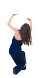 Back view of woman  protects hands from what is falling from abo Stock Images
