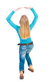 Back view of woman protects hands from what is falling from abo. Ve. woMan holding a heavy load Rear view people collection. backside view of person. Isolated stock photography